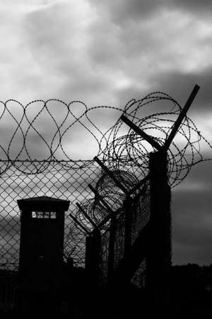 A highly secure prison with razor wire fence and a watchtower Editorial
