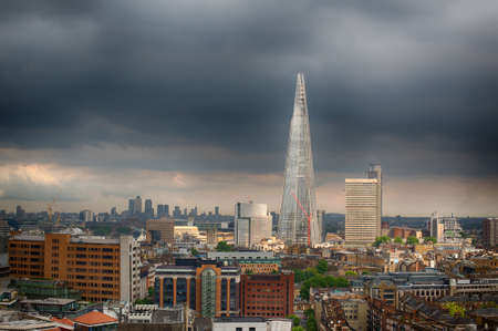 shard: London city skyline with bright light on the buildings and a dark stormy sky behind.