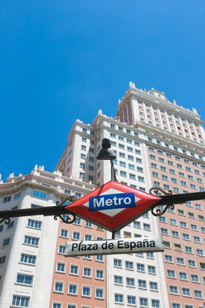 Metro entrance sign at Plaza de Espana in Madrid, Spain with the famous Edificio España in the background.