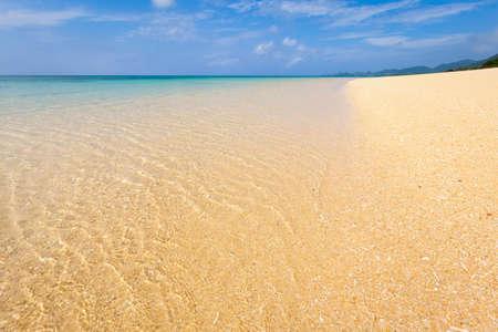 トロピカルな島にある砂浜と透き通ったターコイズブルーの海。フォアグラウンドビーチでの選択的なフォーカス。 写真素材