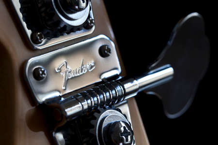 Bath, United Kingdom - May 13, 2011: Fender brand name chased into a metal tuning peg on a Jazz Bass guitar with a black background. Macro close-up with selective focus on the trademark.