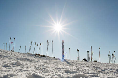 Skis and poles planted into the snow at the side of the piste in Austria with a bright Sun int the sky