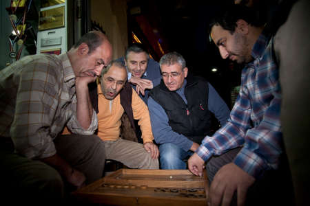 ISTANBUL, TURKEY - NOVEMBER 6, 2009: Group of men involved in an evening game of backgammon played on a street outside a shop in Istanbul Editorial