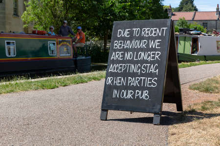 BATH, UK - JUNE 30, 2018 : A chalkboard sign outside a public house on the Kennet and Avon Canal notifying stag and hen parties they are no longer allowed entry due to recent bad behaviour.