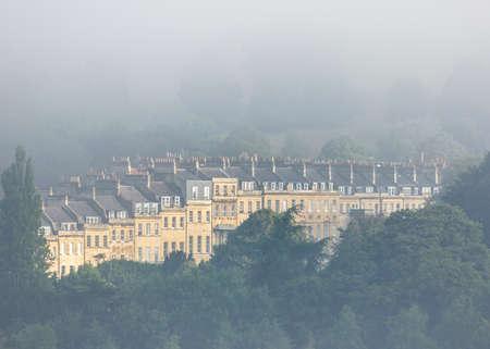 A row of terraced Georgian buildings shrouded in morning mist  in Bath, UK Stock Photo