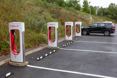 SARN, UNITED KINGDOM - AUGUST 2, 2018 : A row of Tesla Superchargers next to empty parking bays at the Sarn Park motorway services off the M4 near Bridgend in Wales. Editorial