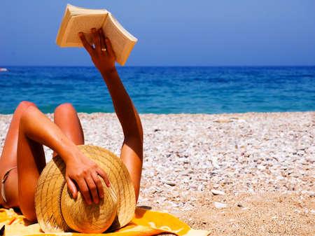 Pretty girl reading novel at beautiful beach Stock Photo