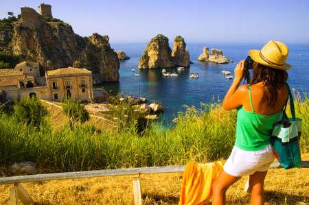 Beautiful girl wearing sun hat taking photo of dramatic european coastal scene Stock Photo