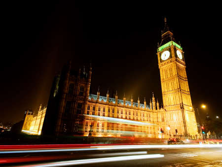 Big Ben, London at night time with Red Bus travelling by...