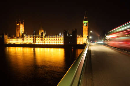 Big Ben, London at night time with Red Bus travelling by... photo