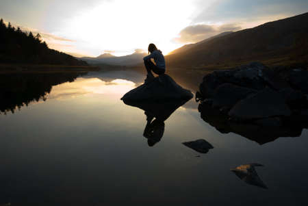 Beautiful girl on mountain lake at sunset Stock Photo