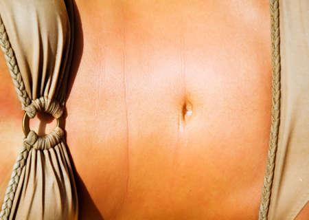 Toned torso of a tanned female photo