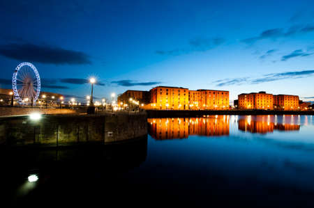 Liverpool Albert dock cityscape at night with view of Maritime Museum and Ferris Wheel Stock Photo