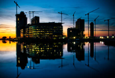 high rise buildings: Dynamic architectural designed modern corporate buildings with construction and cranes in background