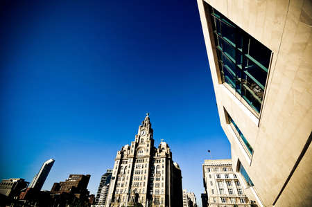An interesting view over the historical Royal Liver building, the Liverpool tourism attraction, on a blue sky background. Stock Photo