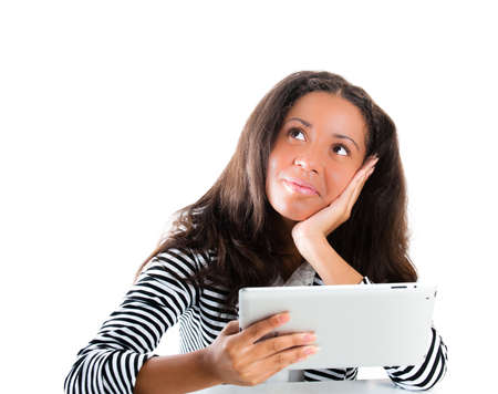 Beautiful mixed race teen girl, working with a portable tablet computer whilst daydreaming - isolated on white photo