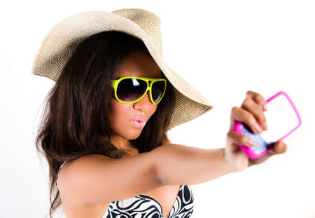 Beautiful young brunette woman in cowboy hat and sunglasses taking a photograph with a mobile cell phone - isolated on white Stock Photo