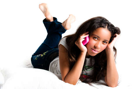 crossed legs: Concerned teenage girl on a pink cell phone lying down listening with legs crossed feet in the air - isolated on white
