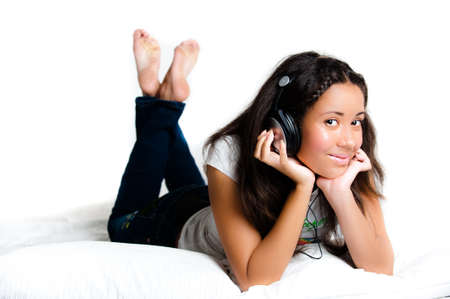 pretty teenage girl with headphones lying down listening to music with legs crossed feet in the air - isolated on white