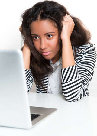 Beautiful mixed race teen girl, looking at a laptop computer, hands in hair, elbows on a desk looking frustrated Stock Photo