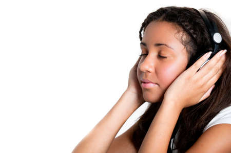 teenage girl with headphones and eyes closed, listening to music with hands over ears photo