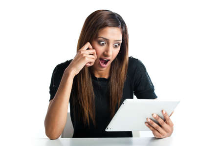 Attractive young asian indian teenage woman, looking shocked at tablet computer