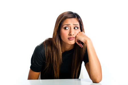 Young beautiful unhappy Asian Indian teenager glancing with face resting on hand