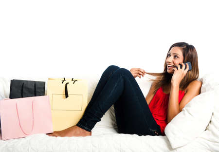 Beautiful happy asian teenage girl lying on the sofa, with shopping bags, listening on the phone and playing with hair Stock Photo