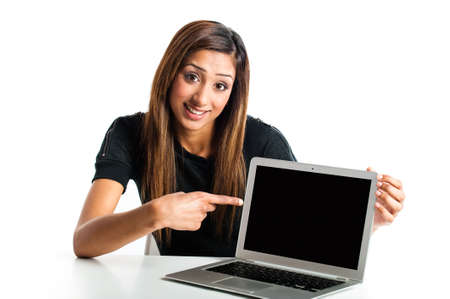 Attractive young asian indian teenage woman, working with a portable tablet computer looking angry and frustrated photo