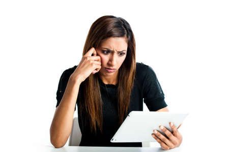 Attractive young asian indian teenage woman, working with a portable tablet computer looking angry and frustrated Stock Photo
