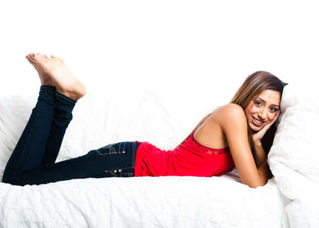 Beautiful asian indian teenage girl lying down on the sofa with feet in the air, smiling, propping her head up photo