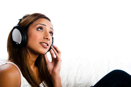 Beautiful asian indian teenage girl, listening to music with hand to headphone looking up and listening.