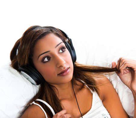 Beautiful asian indian teenage girl, listening to music holding her hair photo