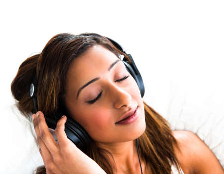 Beautiful asian indian teenage girl, listening to music with her eyes closed photo