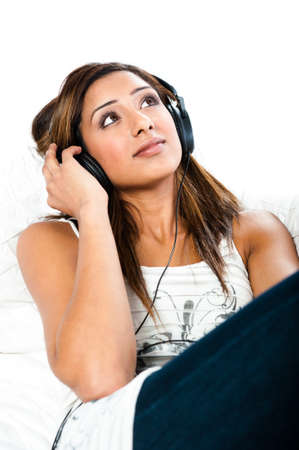 Beautiful asian indian teenage girl, listening to music with her eyes open sitting photo