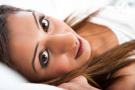 Close-up of fresh beautiful young Asian Indian model, lying down with hand in hair