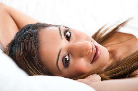 Close-up of fresh beautiful young Asian Indian model, smiling and lying down  photo