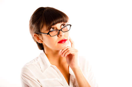 Close up of a young business woman in white, glasses and red lips thinking, with hand to face photo