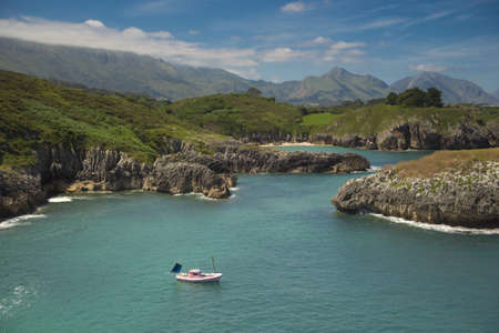 northern spain: A peaceful and sunny day in Asturias Spain. The tranquility than can be Breathed is astonishing. The sea is quite calm, and does not rock the boat. Otherwise, the mountains, just a few meters from the shore, at Their peaks are foggy. Stock Photo