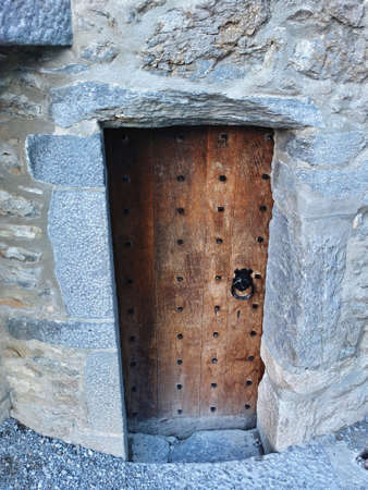 unyielding: Old Castle wooden Door in stone wall with knocker