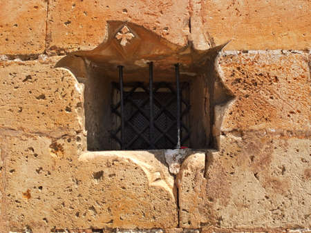 window bars: Castle wall with window bars and carved flower in stone, with locked padlock on the window bars Stock Photo