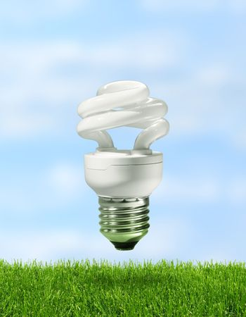 Energy saving compact fluorescent lamp over green grass with blue sky background photo