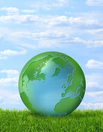 Green-blue planet Earth on green grass and blue sky background photo