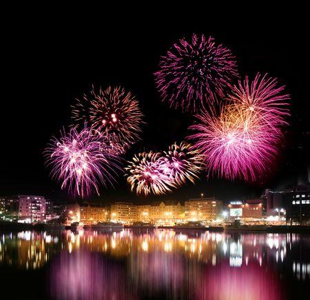 fuegos artificiales: Noche de fuegos artificiales sobre la ciudad con la reflexi�n de aguas tranquilas