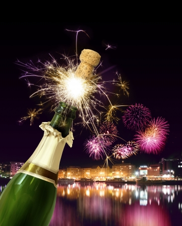 Champagne bottle cork popping with sparkling New Year fireworks photo