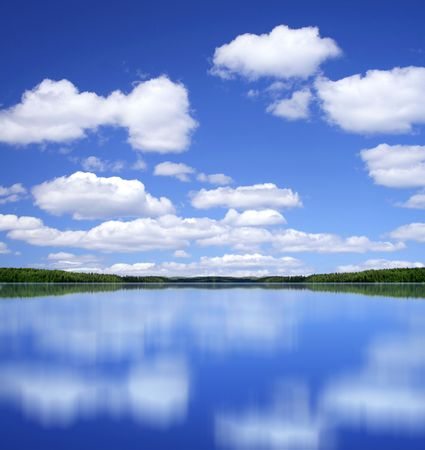 Blue summer sky with white clouds mirror perfect reflection from lake surface