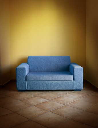 Blue vintage sofa on terracotta tiled floor in yellow room Stock Photo - 7693666