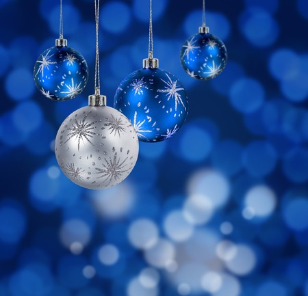 group of christmas baubles: Blue and silver Christmas balls hanging against blue light spots background