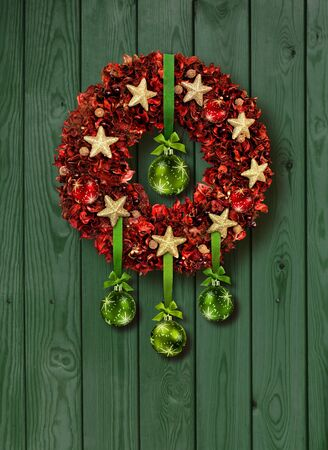 Red Christmas garland with green glass balls on old wooden door photo