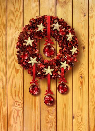 Red Christmas garland with glass balls on old wooden door photo